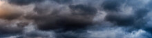 Wide Panoramic View Of The Dark Dramatic Stormy Sky With Cumulus Clouds And Crimson Glow. Sad Cloudscape Overcast