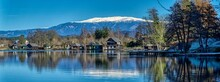 Lake With Boat Huts And Snow Covered Mountains In Late Autumn