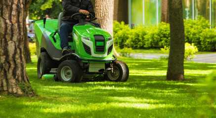 Professional worker trimming green grass with lawn mower m tractor in the park.