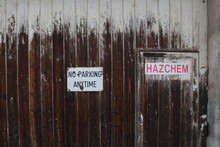 Red, Black And White No Parking Any Time And Hazchem Signs On Old Wooden Door Of Abandoned Industrial Building