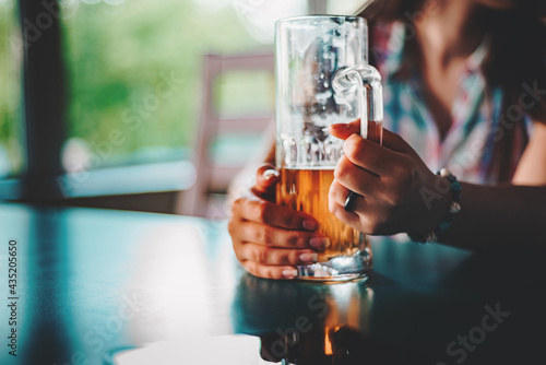Valokuvatapetti woman holds a glass of beer in his hand at the bar or pub