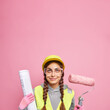 canvas print picture - Satisfied female builder or architect keeps head safe in helmet wears protective glasses holds paint roller and blueprint supplies best service ever uses tool for repair ready for challenges