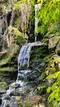 A Waterfall Among Rocks And Vegetation.