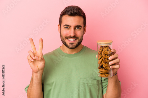Fotografiet Young caucasian man holding cookies jar isolated on pink background showing number two with fingers