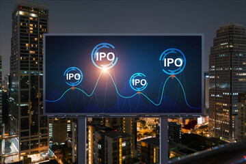 IPO icon hologram on road billboard over night panorama city view of Bangkok. The hub of initial public offering in Southeast Asia. The concept of exceeding business opportunities.