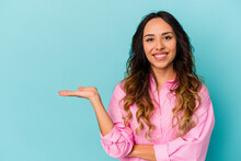 Young Mexican Woman Isolated On Blue Background Showing A Copy Space On A Palm And Holding Another Hand On Waist.