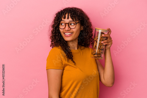 Fotografie, Obraz Young mixed race woman holding a cookies jar isolated on pink background looks aside smiling, cheerful and pleasant
