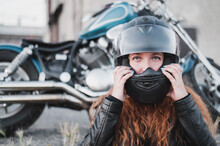 A Red-haired Woman Puts On A Helmet For Safe Motorcycle Riding.