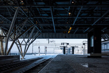 An Empty Railway Station Platform, Looking Out At The Snow-covered Railroad Tracks