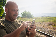 Close-up Of A Stocky Middle-aged Caucasian Man Using A Smartphone Near A Train Track.