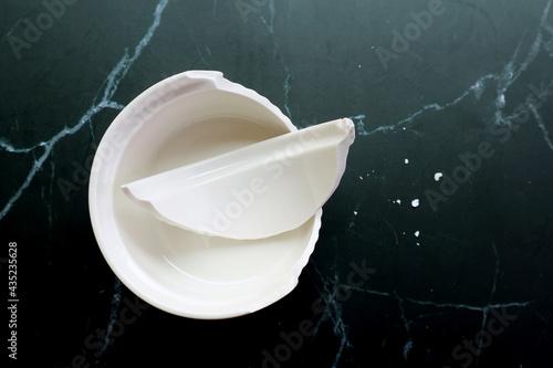 Canvastavla Broken white ceramic baking bowl with fragments on black marble floor