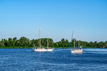 Two White Yachts Sail In The Blue Water Of The Dnieper River Off The Coast Of Kherson (Ukraine). Ships With People On The Deck Against The Backdrop Of A Beautiful Landscape With A Green Shore