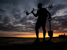 Beautiful Landscape Photo With The Silhouette Of A Man Holding A Metal Detector And A Shovel In Nature.