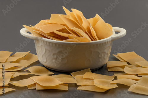 Raw uncooked flat square pasta in bowl Fototapet
