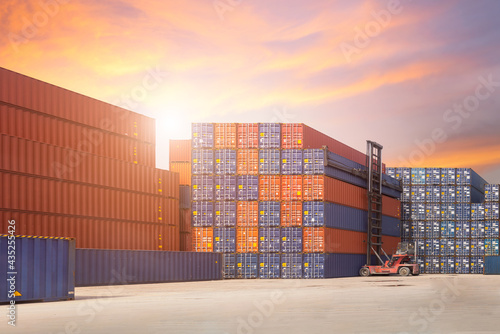 Fototapeta Forklift container loading and unloading cargo into the import-export zone in ya