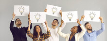 Sharing Experiences And Ideas. Interracial Colleagues Hold A White Layout With Light Bulbs Symbolizing A New Idea. Group Of People Expressing Their Opinion Holding Posters On A Gray Background.