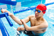 Disabled Latin Man Paralympic Athlete Wearing Cap And Goggles In A Swimming Training  Holding On Starting Block In The Pool In Disability Concept With Hand Hypoplasia