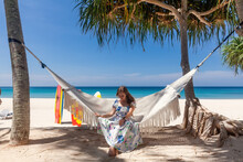 Travel Woman In Dress Sitting On White Hammock On Sandy Beach With Blue Sea And Tropical Trees. Female Smiling And Relax Between Palm Trees In Sunny Day On Vacation, Phuket Island, Thailand