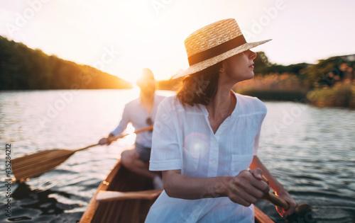 Foto Enjoy paddling canoe on the sunset lake