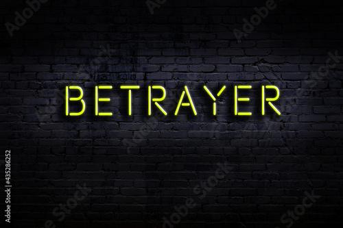 Neon sign. Word betrayer against brick wall. Night view Fototapeta