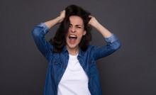 Close Up Portrait Of Screaming Young Woman In Casual Wear While She Holds Her Head In Depressive Mood