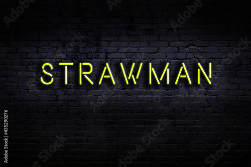 Fotografiet Night view of neon sign on brick wall with inscription strawman