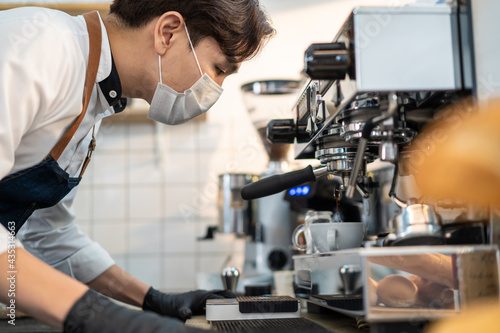 Asian male barista wearing face mask operating coffee machine in cafe Fototapet
