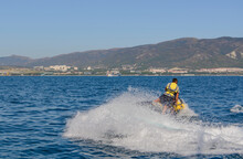 A Tourist During A Vacation Rushes Across The Sea Against The Backdrop Of Mountains In A Protective Suit On A Jet Ski Raising Splashes On A Hot Summer Day. Image Blurring