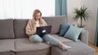 Blonde girl sitting on the couch, working on a laptop. Remote work online