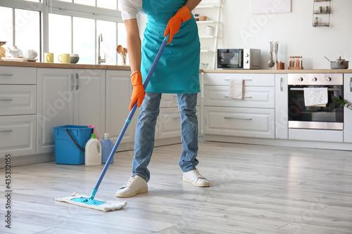Young man mopping floor in kitchen Fototapeta