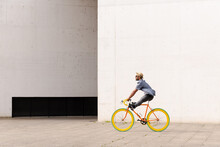 Happy Hispanic Man Riding A Vintage Colorful Bicycle. Urban Ecologic Transport And Sustainable City Concept. Copy Space On White Wall.