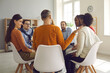 Leinwandbild Motiv Close-up rear view on discussion. Group therapy session. Diverse multiethnic people sitting in circle and talking. Young caucasian man sharing problem to receive help and support from team