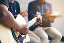 Christian Family Worship God In Home With  Playing Guitar, And Holding Holy Bible .Group Christianity People Reading Bible Together.Concept Of Wisdom, Religion, Reading, Imagination.