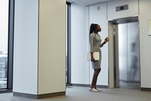 Minimal Full Length Portrait Of African-American Businesswoman Waiting For Elevator In Office Building And Holding Coffee Cup, Copy Space
