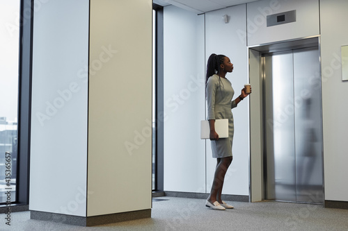 Minimal full length portrait of African-American businesswoman waiting for eleva Fotobehang