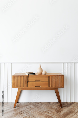 Obraz na plátne Wooden sideboard table with books and a vase
