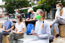 Students In Protective Masks Record Lecture While Sitting On A Stone Street Parapet