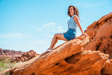 A Young Woman Enjoys A View Of The Valley Of Fire In Nevada, Views Of Ribbons Of Red Rock Slice Through The Desert Landscape.