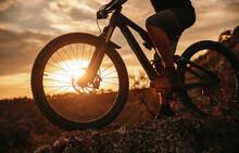 Crop Man Riding Bicycle At Sunset