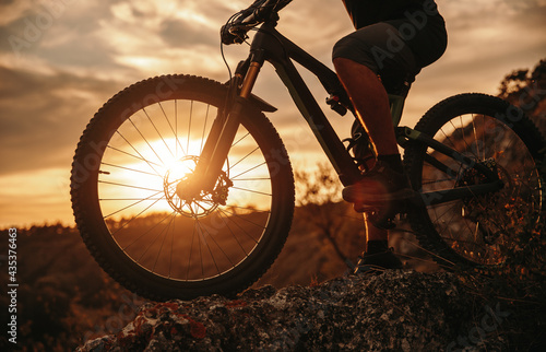 Fotografija Crop man riding bicycle at sunset