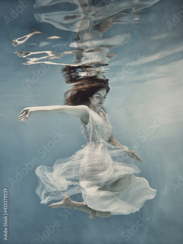 Billede på lærred A girl with long dark hair in a white dress with glitters floats underwater as i