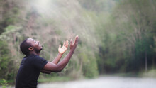 African Man Praying For Thank God In The Green Nature Background