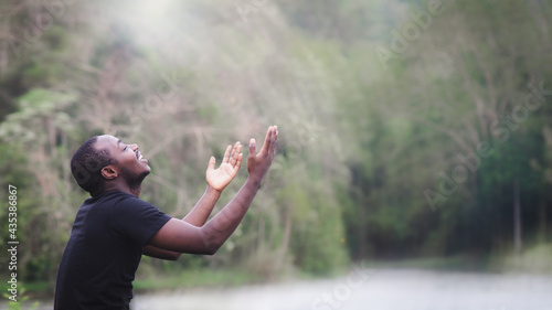 Fotografie, Obraz African man praying for thank god in the green nature background