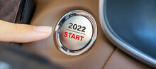 Finger Press A Car Ignition Button With 2022 START Text Inside Modern Electric Automobile. New Year New You, Resolution, Change, Goal, Vision, Innovation And Planning Concept