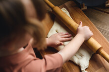 Close-up Of A Little Girl's Hand Rolling Out The Dough. Mother Teaches Preschool Girl To Cook Baked Goods