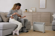 Happy Couple Sitting On Sofa Near Electric Heater At Home