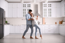 Happy Couple Dancing Barefoot In Kitchen. Floor Heating System