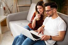 Happy Young Couple With Laptop At Home. Boyfriend And Girlfriend Watching Movie On Laptop..