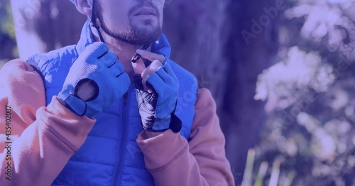 Composition of caucasian man putting helmet on bicycle in forest