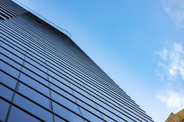 Fototapeta na wymiar Glass skyscraper against blue sky, view from bottom